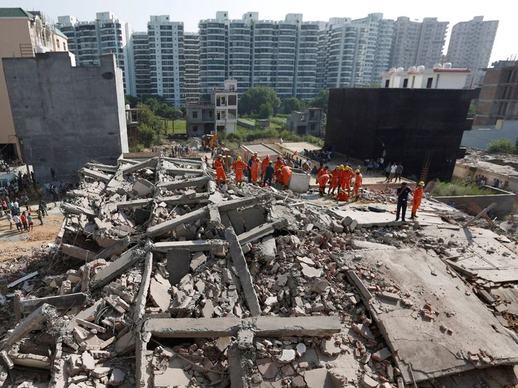 Rescue workers look for survivors at the site of the collapse at Shah Beri village in Greater Noida