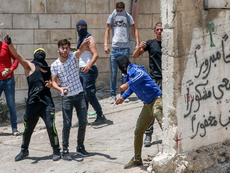 Palestinian protesters throw rocks during clashes with Israeli security forces following a funeral in the village of Beit Ummar, north of Hebron in the occupied West Bank city on July 14, 2018. (Photo by HAZEM BADER / AFP) (Photo credit should read HAZEM BADER/AFP/Getty Images)