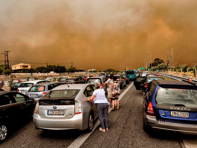 Cars are blocked at the closed National Road during a wildfire in Kineta, near Athens, on July 23, 2018