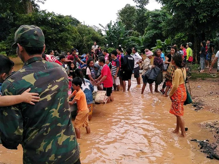 Villagers carry their belongings as they evacuate after the Xepian-Xe Nam Noy hydropower dam collapsed in Laos