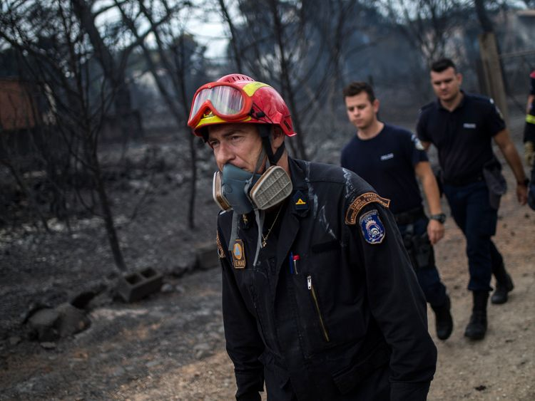 Rescuers arrive at the area where dead bodies were found following a wildfire at the village of Mati, near Athens, on July 24, 2018