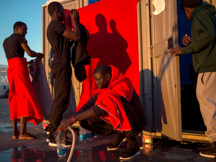 Migrants rescued at sea use mobile bathroom facilities at the harbour of Algeciras