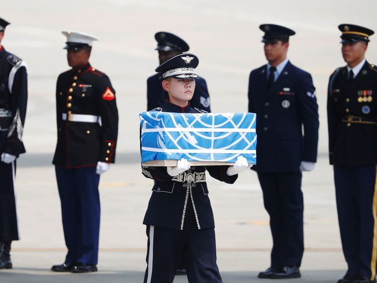 The remains were carried in boxes covered in blue United Nations flags