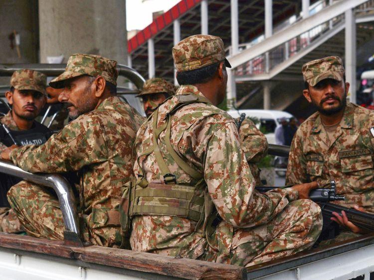 Pakistani soldiers sit on a truck during a patrol on a street in Rawalpindi