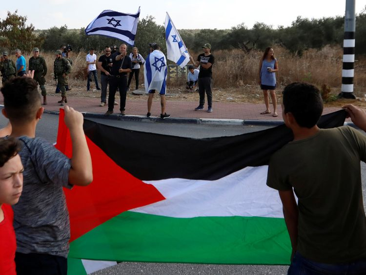 Palestinians stand in front of Israelis as they wait for the release of Palestinian teenager Ahed Tamimi from an Israeli prison, at Rantis checkpoint in the occupied West Bank