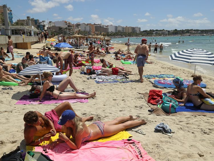 Tourists relax at the beach in Palma, Mallorca, where temperatures are likely to soar in August