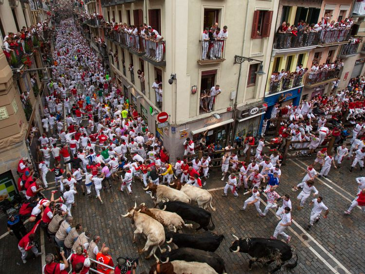 Hundreds of people take part in the running of the bulls each day during San Fermin