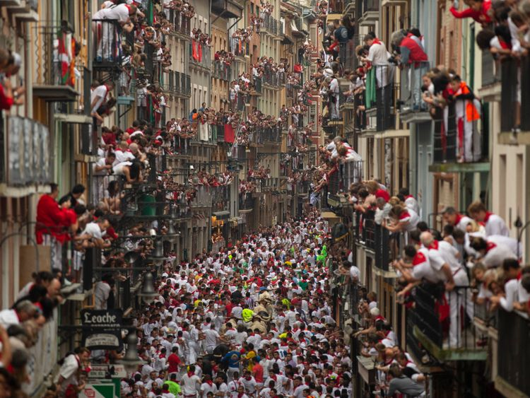 People hang out of their windows to watch the running of the bulls