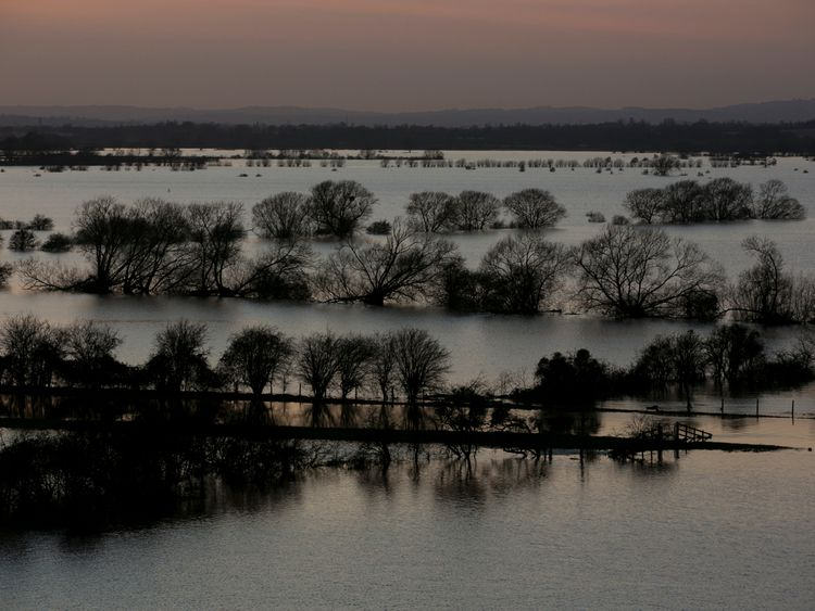 The sun sets over flooded fields surrounding the River Tone that has burst its banks on the Somerset Levels in 2014
