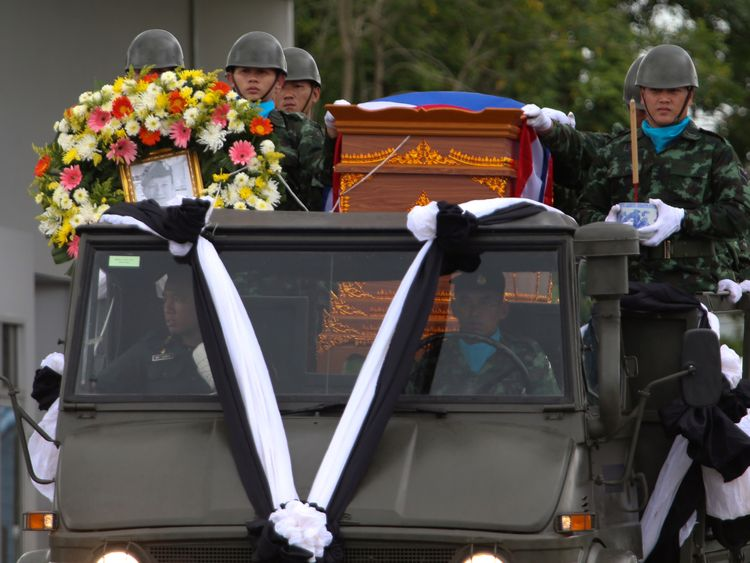 An honour guard carries the coffin of diver Saman Gunan