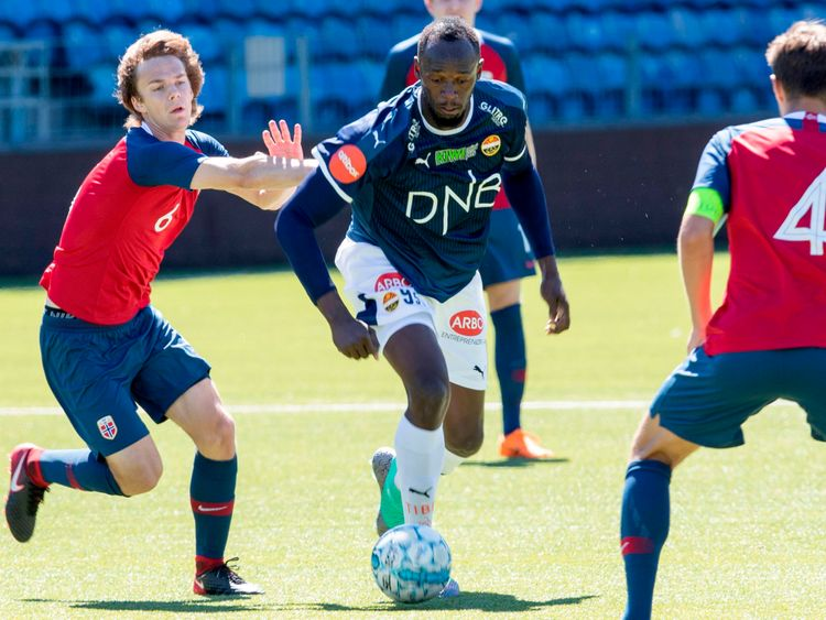Usain Bolt and Norway's Fredrik Horn Myhre (L) vie for the ball during a friendly game