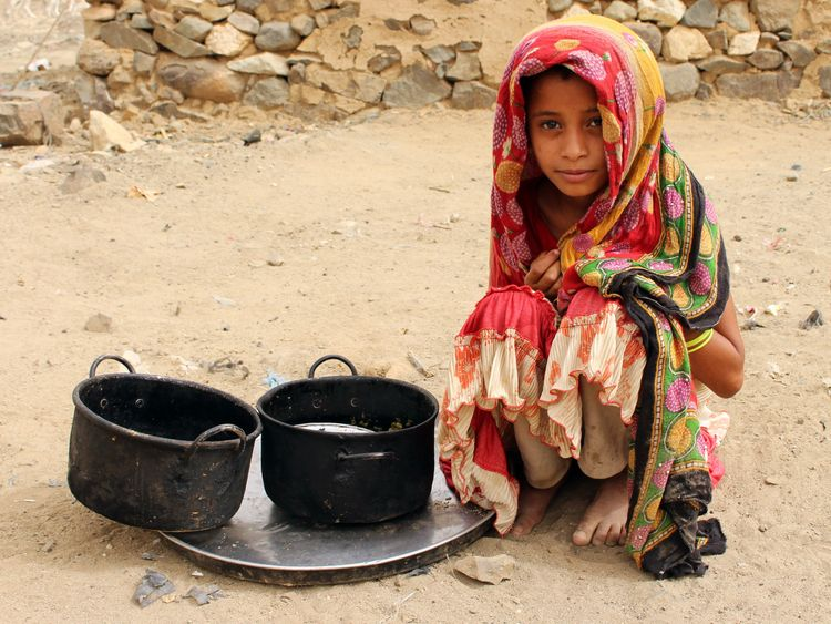 A displaced Yemeni child sits next to pots of food at a make-shift camp in the northern district of Yemen's Hajjah province on July 7, 2018