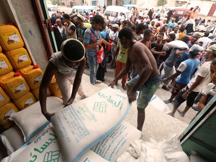 Workers unload sacks of wheat flour as people gather outside an aid distribution centre in the Red Sea port city of Hodeidah, Yemen June 14, 2018