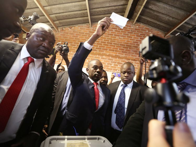 Nelson Chamisa held his ballot paper in the air as he voted in Harare