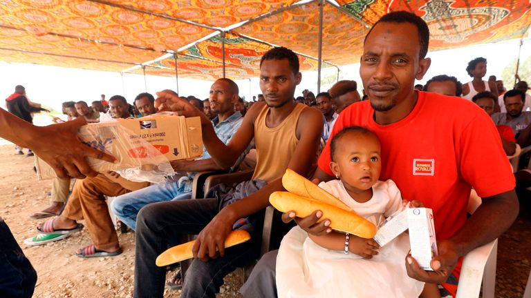 Illegal African migrants receive bread rations at an Anti-Illegal Immigration Authority shelter in Ain Zara in the Libyan capital Tripoli on July 22, 2018