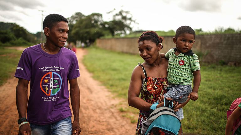 Former slave Elenilson de Conceição (L) walks with family members before departing on his journey on April 9, 2015 in Monsenhor Gil, Piauí state, Brazil