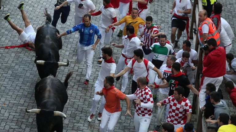 Runners sprint along the bulls during the last running of the bulls at the San Fermin festival in Pamplona, Spain, July 14, 2018. REUTERS/Susana Vera
