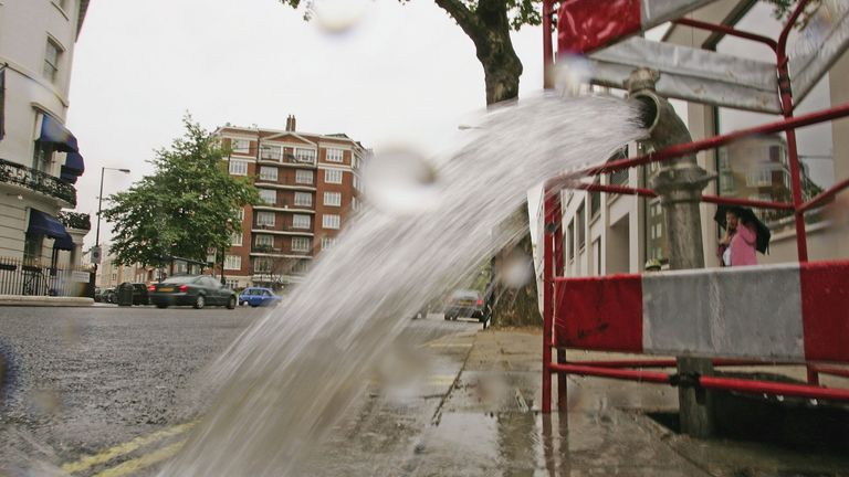 Burst pipe spews water onto a street
