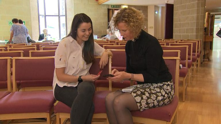 Rev Margaret Cave takes a contactless payment from a church member