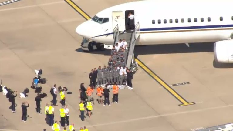 England players pose for photos after disembarking from their plane