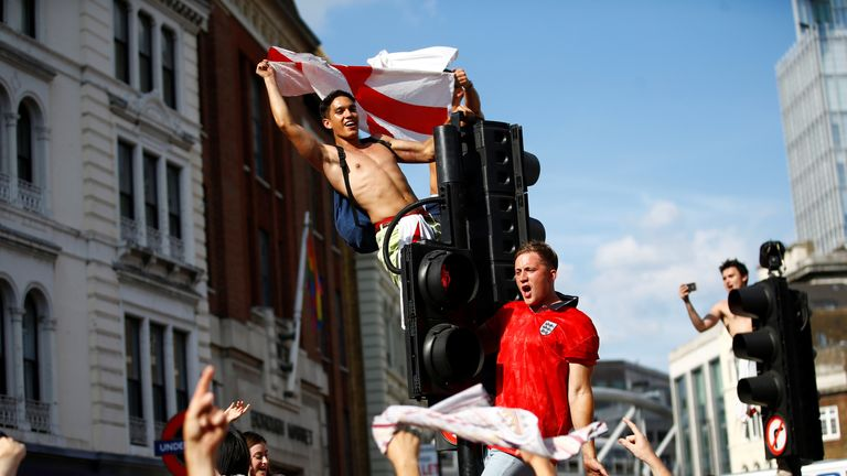 England fans watch Sweden vs England - London, Britain - July 7, 2018 England fans celebrate by climbing traffic lights after the match REUTERS/Henry Nicholls