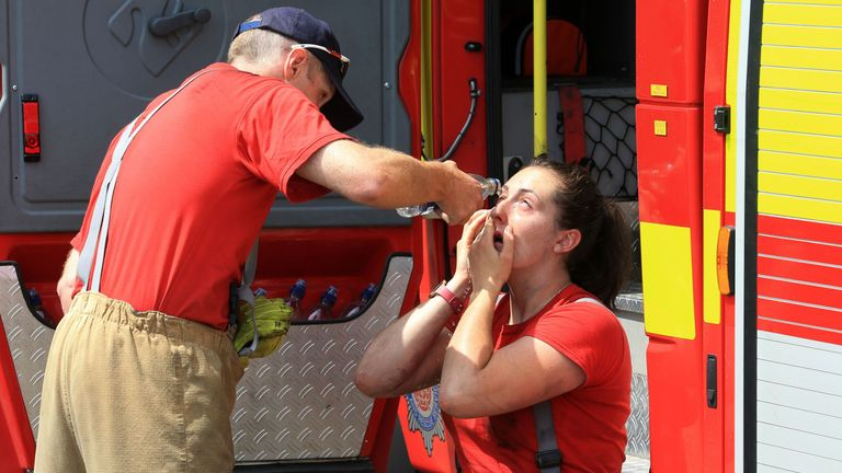 A crew member washes the eyes of a firefighter
