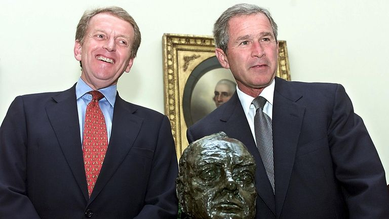 George W. Bush (R) smiles after receiving a bust of Sir Winston Churchill from British Ambassador to the US Christopher Meyer at the Oval Office of the White House in Washington in 2001