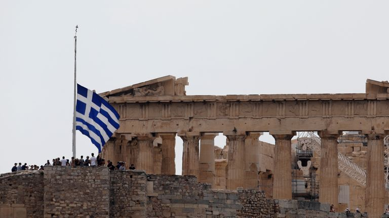 A Greek national flag flies at half mast in front of the Parthenon temple atop the Acropolis hill, as a period of national mourning is declared for the victims of wildfires, in Athens, Greece, July 25, 2018. REUTERS/Costas Baltas