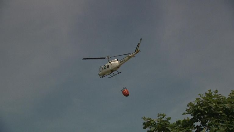 A helicopter carries a basket of water to help douse the flames