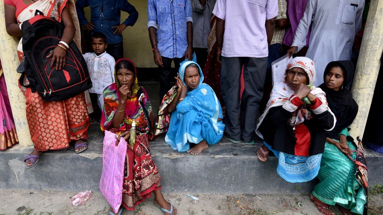 Villagers wait outside the National Register of Citizens (NRC) centre to get their documents verified