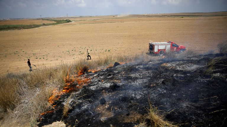 Israeli firefighters attempt to extinguish a fire burning scrubland in an area where Palestinians have been causing blazes by flying kites and balloons loaded with flammable materials, on the Israeli side of the border between Israel and the Gaza Strip July 20