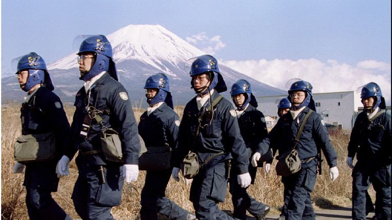 A police squad leave a Aum Shinri Kyo (Supreme Truth Sect) compound after finishing their shift in the small village of Kamikuishiki at the foot of Mount Fuji in this March 28, 1995 file photo