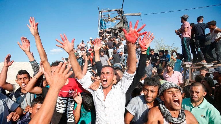 Palestinians react with bloodied hands outside a Hamas outpost that was struck by Israeli bombardment near Khan Yunis in the southern Gaza Strip on July 20, 201