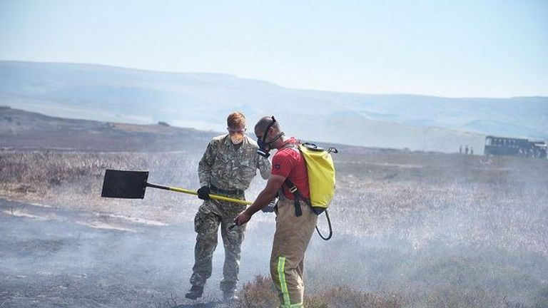 Firefighter working with soldier on Saddleworth Moor. Pic: Manchester Fire
