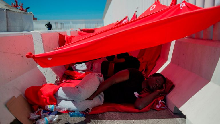 A man rescued at sea with other migrants rests as he waits to be transferred at the harbour of Algeciras