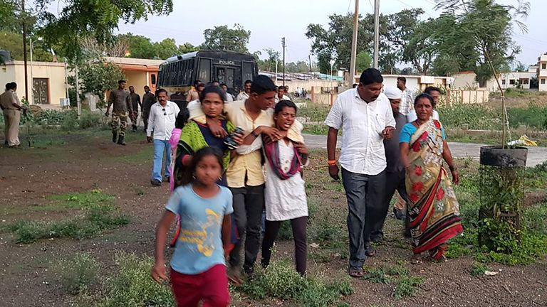 Women whose relatives were murdered in a lynching incident are led away from the crime scene area by villagers in Dhule district