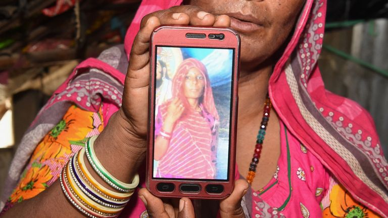 Mohinidevi Nath displays a photo on a mobile phone of her cousin Shantadevi Nath, who was killed by a mob that falsely believed she was intent on abducting children, on the outskirts of Ahmedabad in India's western Gujarat state on June 27, 2018