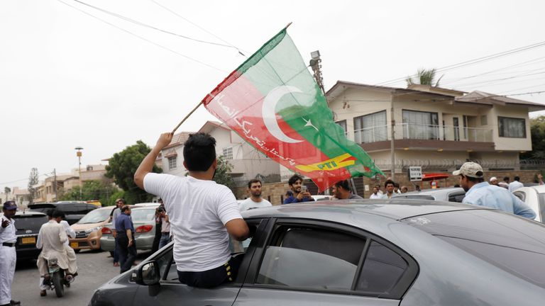 A supporter of Pakistan Tehreek-e-Insaf (PTI) waves the party flag from the window of a car outside a polling station during the general election in Karachi, Pakistan, July 25, 2018. REUTERS/Akhtar Soomro