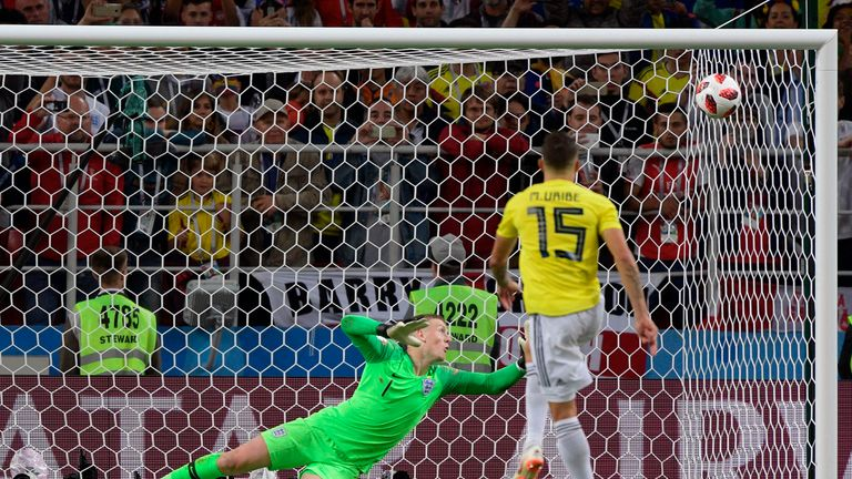 England's goalkeeper Jordan Pickford stops Colombia's midfielder Mateus Uribe's shot