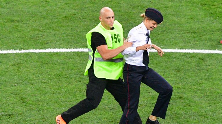 A pitch invader of the Pussy Riot group is escorted by a steward during the World Cup final