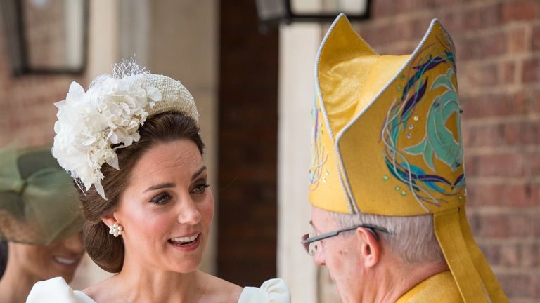 Kate speaks to the archbishop while holding Louis