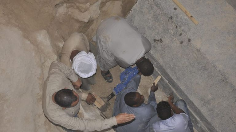 Egyptian excavation workers outside the site of the newly discovered giant black sarcophagus