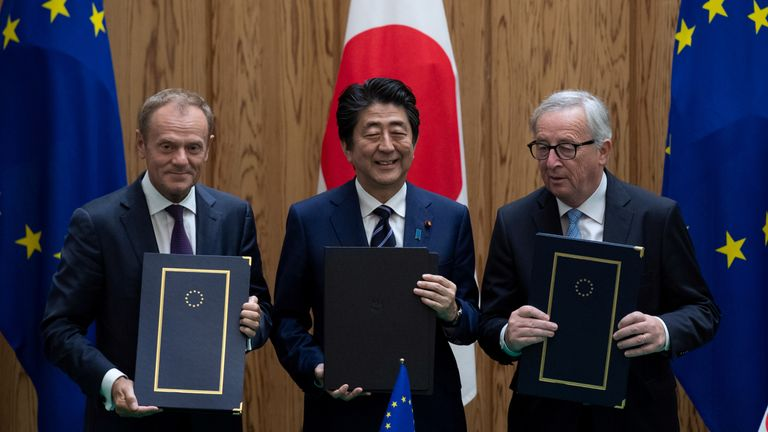 Mr Abe shows off the deal with European Commission President Jean-Claude Juncker and European Council President Donald Tusk