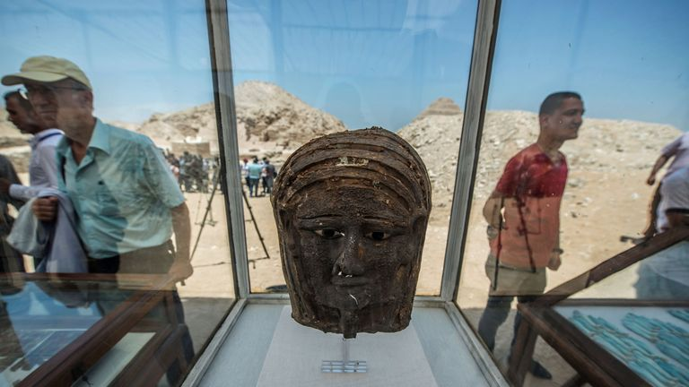 A picture taken on July 14, 2018 shows a gilded silver mummy mask found on the face of the mummy of the second priest of Mut on display in front of the step pyramid of Saqqara, south of the Egyptian capital Cairo. - The Egyptien Minister of Antiquities announced the excavation of a mummification workshop discovered along with a communal burial place, consisting of several burial chambers. The work is being carried out south of the King Unas Pyramid in Saqqara by an Egyptian-German mission. (Phot