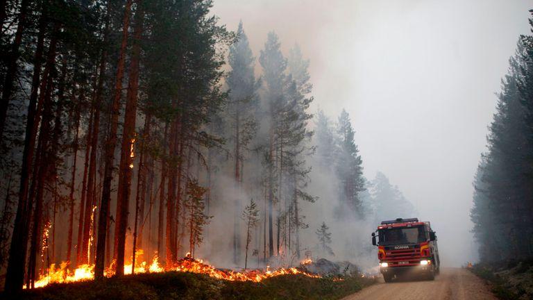 A fire engine is seen as fire burns in Karbole, Sweden, on July 15, 2018