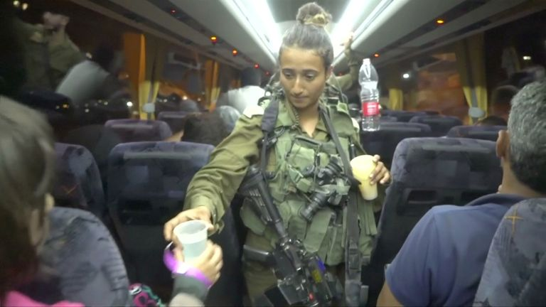 An Israeli solider hands out water on a bus, during the Syria Civil Defence, also known as the White Helmets, extraction from the Golan Heights, Israel in this still image taken from video, provided by the Israeli Army July 22, 2018. Israeli Army Handout via REUTERS ATTENTION EDITORS - THIS IMAGE WAS PROVIDED BY A THIRD PARTY. RTV RESTRICTIONS: Broadcasters: NONE Digital: NONE . For Reuters customers only.