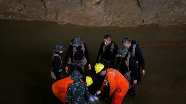 Soldiers and rescue workers work in Tham Luang cave complex, as an ongoing search continues