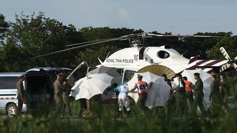 Police use umbrellas to cover a stretcher at a military airport in Chiang Rai