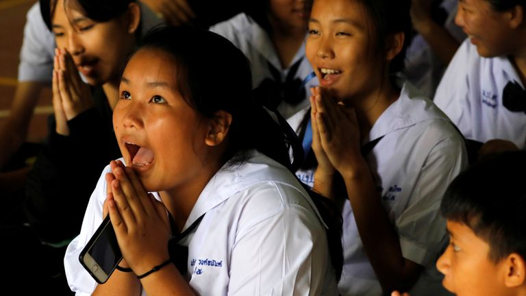 Classmates react after they hear that some of the 12 boys trapped inside the cave have been rescued
