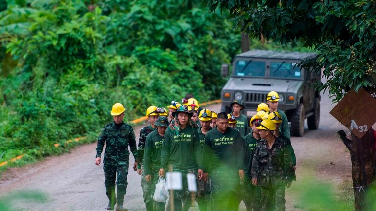 Thai soldiers walking from the cave area as operations restart on Monday